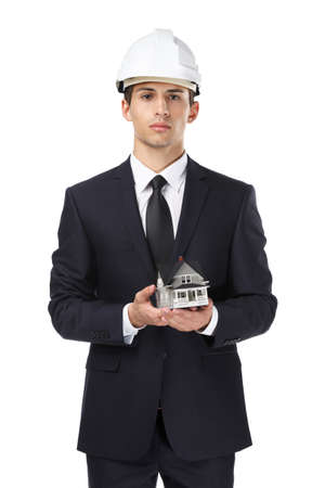 executive helmet: Businessman in white headpiece hands model house, isolated on white. Concept of real estate and engineering
