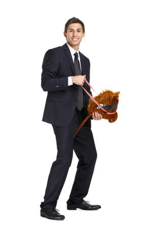 Full-length portrait of businessman riding the toy horse, isolated on white