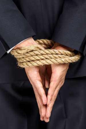 servitude: Close up of bound hands of businessman. Concept of slavery and hard work Stock Photo