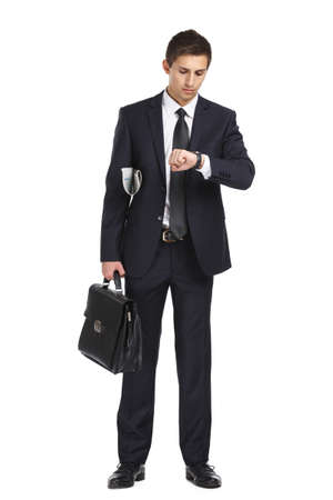 Full-length portrait of businessman handing briefcase and looking at his watch, isolated on white. Concept of business and success photo
