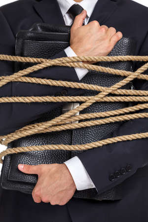 Close up of businessman handing briefcase who tied with the rope, isolated on white. Concept of slavery and violence photo
