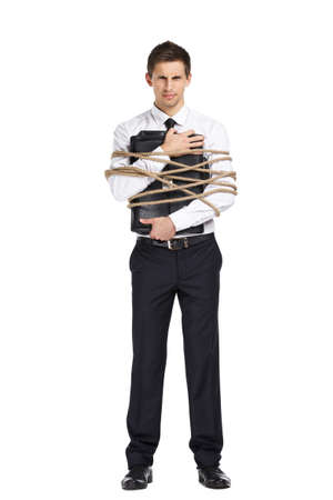 servitude: Full-length portrait of businessman handing briefcase who tied with the cord, isolated on white. Concept of slavery and violence