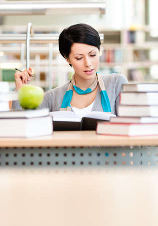 Interested female student with green apple studies sitting at the desk at the reading hall of the library. Knowledge concept photo
