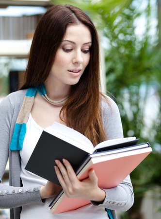Young female student with books at the library. Research. Education photo