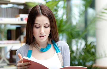 Beautiful female student with books at the library. Research. Education and research photo