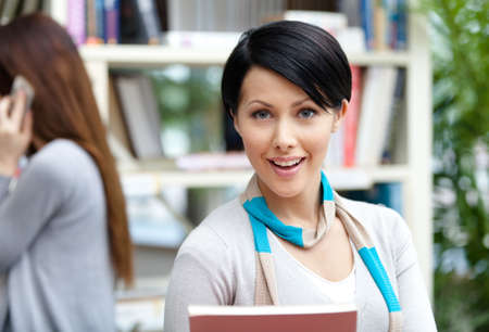 Woman student at the library against bookshelves and her friend. Education and research