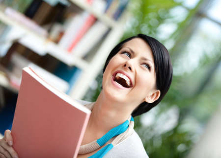 undergraduate: Female undergraduate with book at the library. Education and self-development