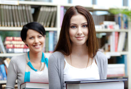 Two pretty girlfriends carry piles of books at the library photo
