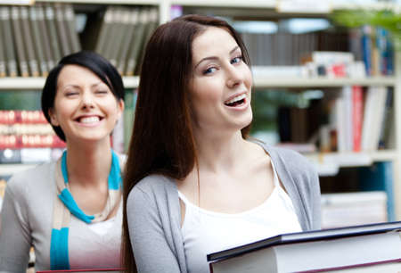 Two laughing girlfriends carry piles of books at the library photo