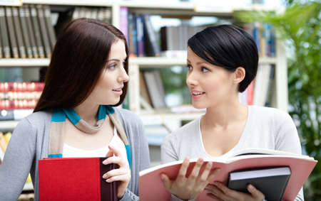 Two female students read books at the library