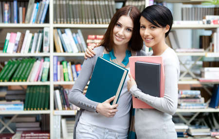 Two girlfriends keeping books hug at the library. Friendship photo
