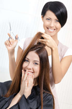 beautician: Beautician cuts hair of woman in hairdressers. Concept of fashion and beauty