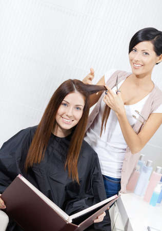 haircutter: Hairdresser cuts hair of woman in hairdressers. Concept of fashion and care Stock Photo