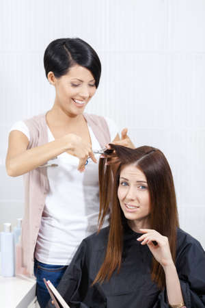 Beautician cuts hair of woman in hairdress salon. Concept of fashion and beauty