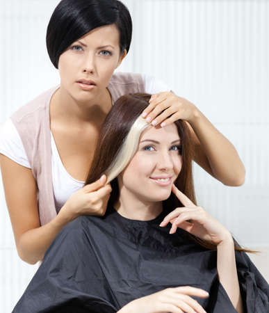 Hair stylist tries lock of dyed blond hair on the client sitting on the chair in the hairdressing salon photo