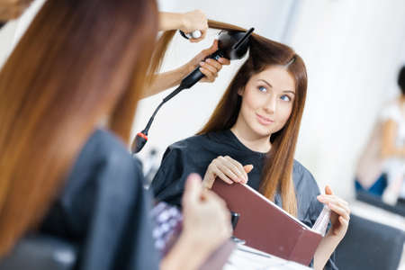 Reflection of beautician doing hair style for woman in hairdress salon. Concept of fashion and beauty photo