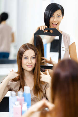 Hair stylist showing the ready haircut of the female client in mirror. Concept of fashion and beauty photo