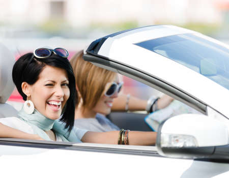 Female friends driving car and having fun on the vacation photo