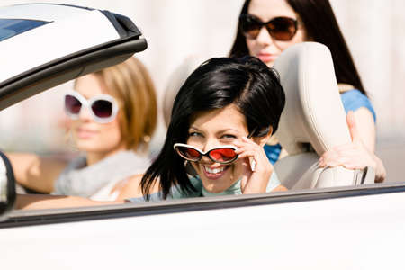 Group of happy girls in the convertible car. Little trip of teenage ladies photo