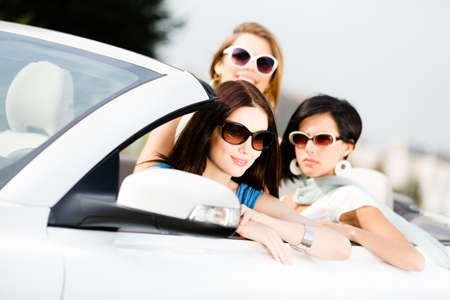 Group of pretty teenagers driving the car. Adorable car trip on vacation photo