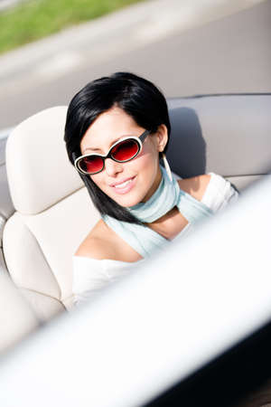 Close up of smiley woman in the white car wearing cute sunglasses photo