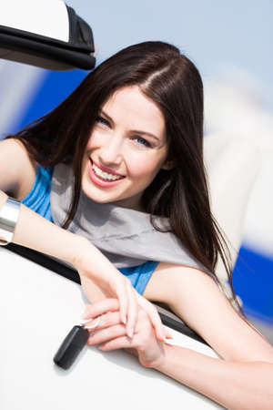 Pretty female driver in a car showing the car key photo