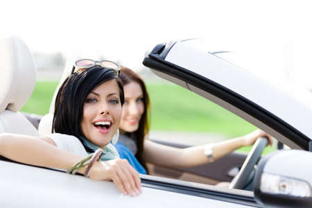 Two happy friends in the convertible car driving everywhere and looking for freedom and fun photo