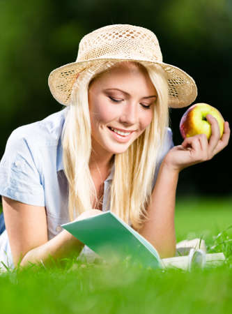 Wearing straw hat girl with healthy apple reads interesting book lying on the grass in the park photo