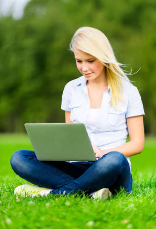 Attractive female student with silver laptop sitting on the grass in the summer park photo