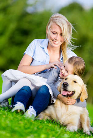 Mother and daughter with retriever sitting on the green grass at the summer park photo
