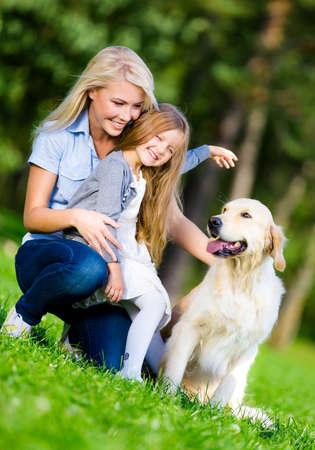 Mother and daughter with labrador retriever sitting on the green grass at the summer park photo