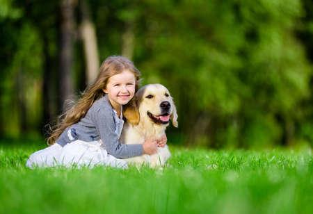 perro labrador: Niña sentada en la hierba con el perro perdiguero de oro en el parque de verano Foto de archivo