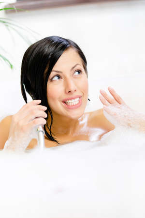 Girl lying in bathtub with suds plays with shower head like phone and relaxes photo