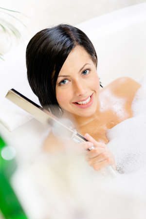Woman lying in bathtub with suds plays with shower head and relaxes photo