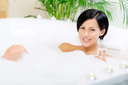 Woman taking a bath with suds and candles drinks champagne and relaxes photo