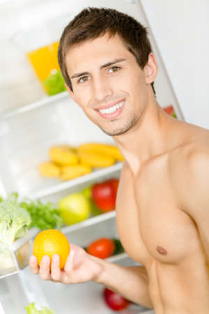 vertical fridge: Man hands orange standing near the opened refrigerator. Concept of healthy and dieting food Stock Photo
