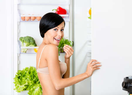 Lady eating near the opened fridge full of vegetables and fruit. Concept of healthy and dieting food photo