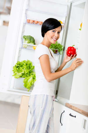 Lady takes red pepper from the opened fridge full of vegetables and fruit. Concept of healthy and dieting food photo