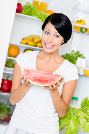 Woman takes watermelon from the opened refrigerator full of vegetables and fruit. Concept of healthy and dieting food photo