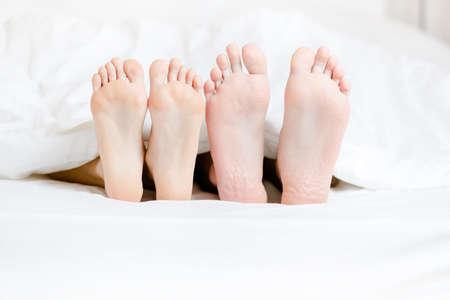 Close up von zwei Paar Füße des Paares nebeneinander im Schlafzimmer