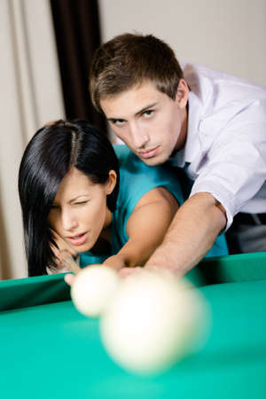 Man teaching lady to play billiards. Spending free time on gambling Stock Photo - 25595918