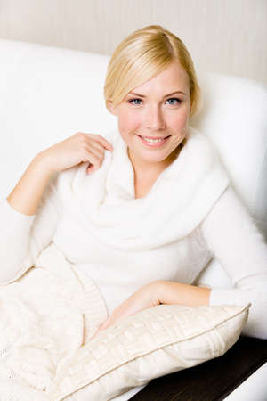 Woman in white sweater sitting on the leather sofa with the pillow under her hand