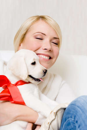 Woman embracing white labrador puppy with red ribbon on the neck photo