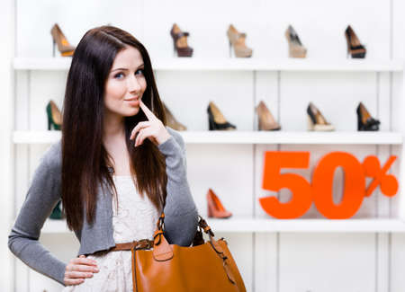 Portrait of woman in shopping center with 50% sale in the section of female heeled shoes. Concept of consumerism and stylish purchase photo