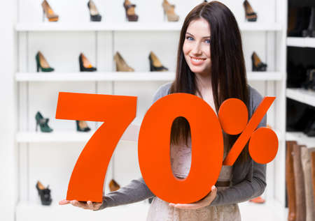 Woman keeps the model of 70% sale on shoes standing at the shopping center against the showcase with pumps photo