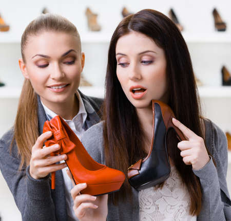 doubtfulness: Salesperson offers high heeled shoes for the female customer in the shopping center