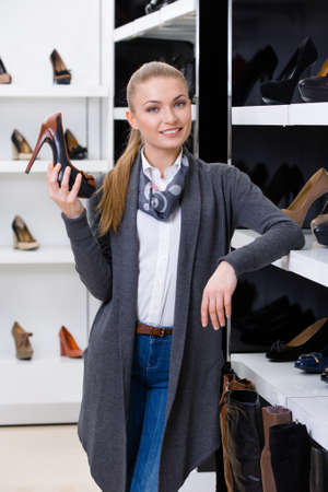 Woman with shoe in hand chooses pumps looking at the shelves with numerous pumps photo