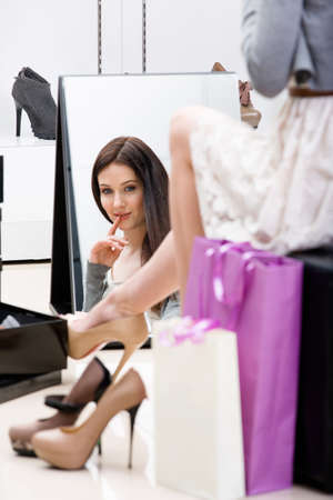 try: Reflection of woman sitting on chair and trying on new footwear in the shop Stock Photo