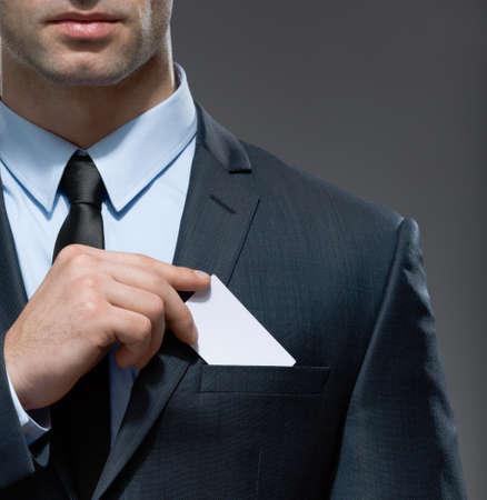 Deel van het lichaam van de man die neemt visitekaartje uit de zak van pak, copyspace