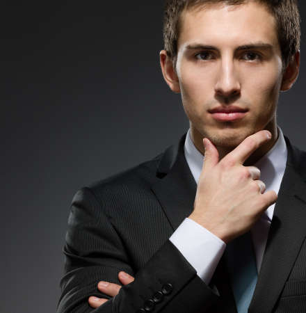 Portrait of pensive business man wearing business suit and black tie touches his face photo